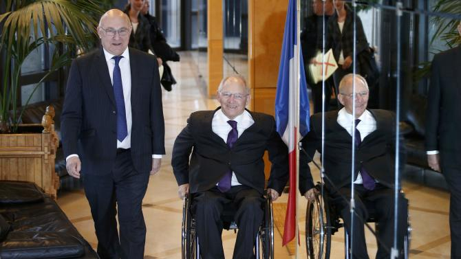 French Finance Minister Michel Sapin and German Finance Minister Wolfgang Schaeuble arrive to attend a meeting at the Bercy Finance Ministry in Paris