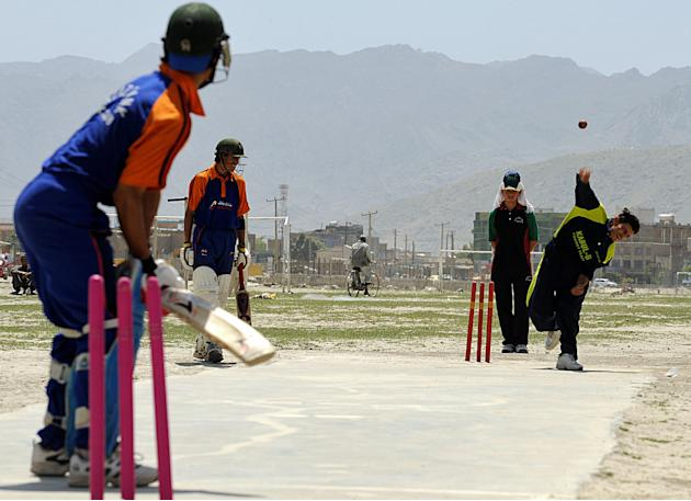 Afghan cricketers take part in a game in
