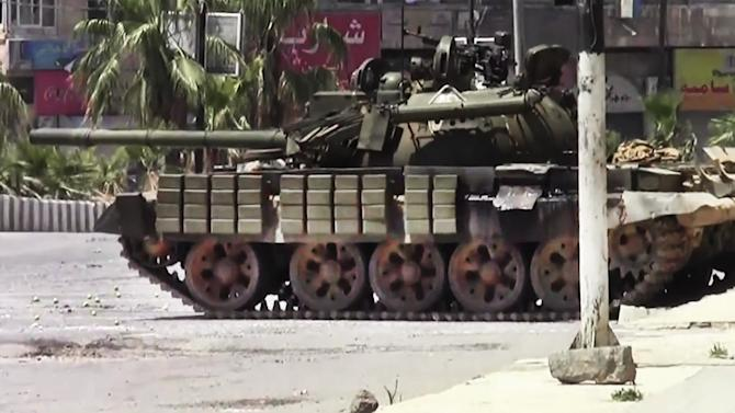 This image made from amateur video released by the Shaam News Network and accessed Sunday, July 29, 2012, shows a Syrian military tank in Daraa, Syria. (AP Photo/Shaam News Network via AP video) TV OUT, THE ASSOCIATED PRESS CANNOT INDEPENDENTLY VERIFY THE CONTENT, DATE, LOCATION OR AUTHENTICITY OF THIS MATERIAL
