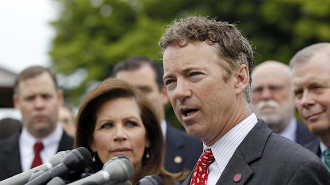 Rep. Michele Bachmann, R-Minn., chairwoman of the Tea Party Caucus, listens at left as while Sen. Rand Paul, R-Ky., speaks during a news conference with Tea Party leaders about the IRS targeting Tea Party groups, Thursday, May 16, 2013, on Capitol Hill in Washington. (AP Photo/Molly Riley)