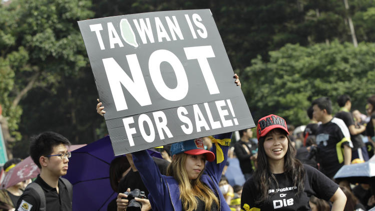 Protesters display a banner denouncing the controversial China Taiwan trade pact during a massive protest in front of the Presidential Building in Taipei, Taiwan, Sunday, March 30, 2014. Over a hundred thousand protesters gathered in a demonstration against the island's rapidly developing ties with the communist mainland. (AP Photo/Wally Santana)