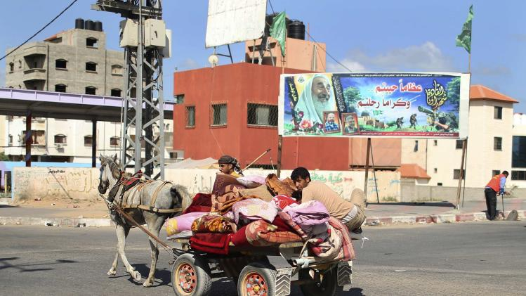 Palestinians, who fled their homes in the northern border town of Beit Lahiya, ride a horse cart on their way to stay at a United Nations-run school in the northern Gaza Strip