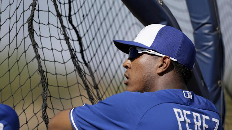 Kansas City Royals' Salvador Perez talks with teammates by the batting cage as he and others take batting practice during spring baseball practice, Friday, March 7, 2014, in Surprise, Ariz. (AP Photo/Tony Gutierrez)