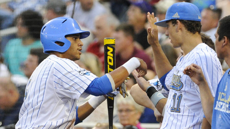 UCLA's Kevin Williams, left, is greeted at the dugout by James Kaprielian (11) after he scored against Mississippi State on a single by Cody Regis in the fourth inning of Game 2 in their NCAA College World Series baseball finals, Tuesday, June 25, 2013, in Omaha, Neb. (AP Photo/Eric Francis)