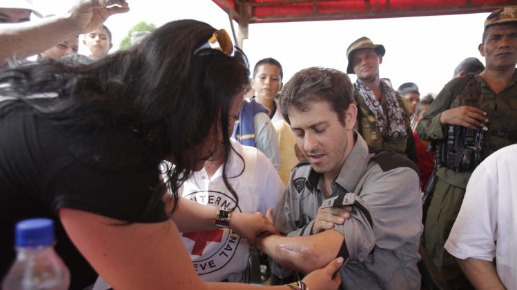 A woman checks a wound on the left arm of French journalist Romeo Langlois after his release by the FARC in San Isidro, Colombia, Wednesday, May 30, 2012. Langlois, who was wounded when he was taken by rebels of the Revolutionary Armed Forces of Colombia, FARC, on April 28 when they attacked troops he was accompanying on a cocaine-lab eradication mission, was handed over by the rebels to a delegation that included a French diplomat. (AP Photo/Fernando Vergara)