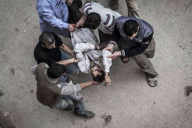 In this Tuesday, Oct. 23, 2012 photo, Syrian residents carry a man severely injured from an artillery shell that landed near a bakery, to a hospital for treatment in Aleppo, Syria. Several were killed and a dozen were injured after the artillery shell that landed near a bakery in Aleppo on Tuesday, Oct. 23, 2012. (AP Photo/Narciso Contreras).