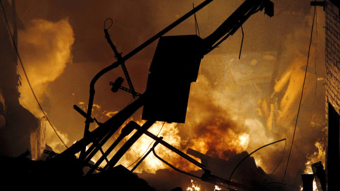 Fire and smoke rise at an upscale shopping district in Kansas City, Mo., where a city official said a gas explosion sparked a block-engulfing blaze, Tuesday evening, Feb. 19, 2013. (AP Photo/The Kansas City Star, Keith Myers) KANSAS CITY OUT