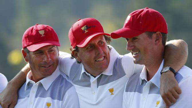U.S. golfer Mickelson puts his arms around team captain Couples and player Simpson during a team photo session prior to their first practice round for the 2013 Presidents Cup golf tournament at Muirfield Village Golf Club in Dublin, Ohio