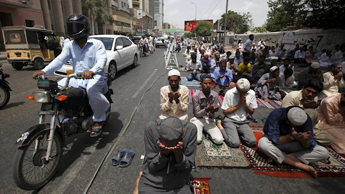 Vehicles move past men offering their Friday prayers near a mosque during the holy month of Ramadan in Karachi