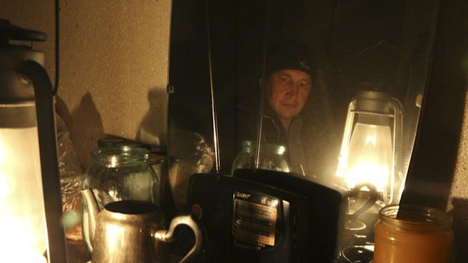 Ravshan, a Crimean Tatar, is reflected in a mirror as he uses a burning oil lamp due to a power cut inside his house in the village of Strogonovka
