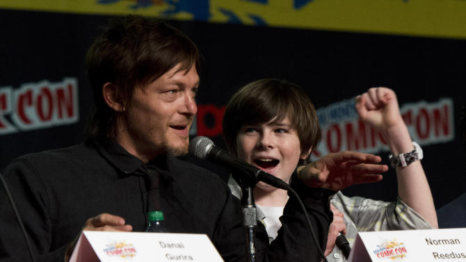 """IMAGE DISTRIBUTED FOR AMC -Norman Reedus, left, and Chandler Riggs of the the AMC show """"The Walking Dead"""" are seen during a panel at NYC-Comic-Con on Saturday, Oct. 13, 2012  in New York. (Photo by Charles Sykes/Invision for AMC/AP Images)"""