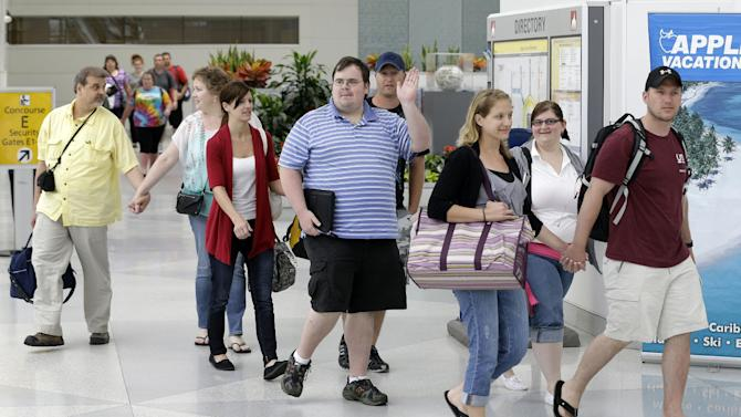Passengers from the Royal Caribbean's Grandeur of the Seas cruise ship, which caught fire during its voyage from Baltimore to the Bahamas, leave a security checkpoint after arriving on a charter flight at Baltimore-Washington International Thurgood Marshall Airport, Tuesday, May 28, 2013, in Linthicum, Md. Royal Caribbean said the fire occurred early Monday and was extinguished after about two hours with no injuries reported. (AP Photo/Patrick Semansky)
