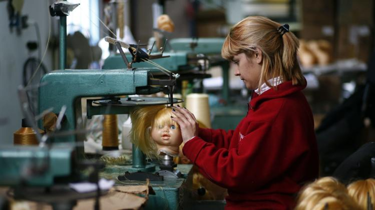 An employee sews a doll's hair to its head inside a toy factory in Buenos Aires