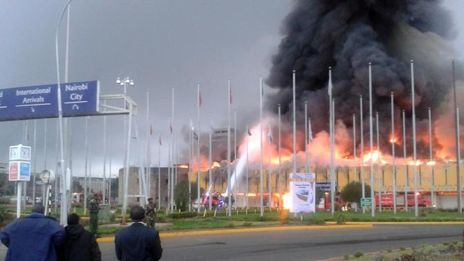 Onlookers watch as black smoke billows from the international arrival unit of Jomo Kenyatta International Airport in Nairobi, Kenya, Wednesday, Aug. 7, 2013. A massive fire engulfed the arrivals hall at Kenya's main international airport early Wednesday, forcing East Africa's largest airport to close and the rerouting of all inbound flights. (AP Photo/Segeni Ngethe)