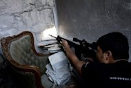A Syrian rebel sniper shoots at forces loyal to Syrian President Bashar al-Assad in the Seif al-Dawla area of the embattled northern Syrian city of Aleppo on September 10. Britain, France and the United States are clamouring for more sanctions on the Assad regime and demand he step down but Russia insists on a negotiated settlement that would involve all the players of conflict