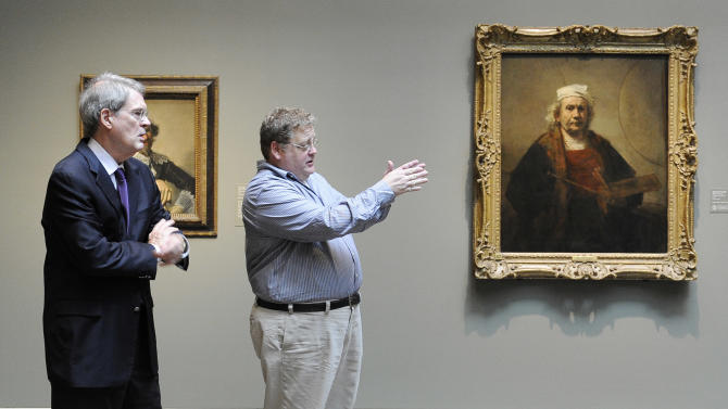 """This May 30, 2012 photo shows Museum of Fine Arts, Houston curator Edgar Peters Bowron, left, and exhibition designer Bill Cochran standing next to Rembrandt's """"Portrait of the Artist"""" at the museaum in Houston. A collection of paintings including works by Rembrandt, Van Dyck and Gainsborough has left its home at London's Kenwood House to travel the U.S. while the stately mansion undergoes renovation. The exhibit opens June 3. (AP Photo/Pat Sullivan)"""