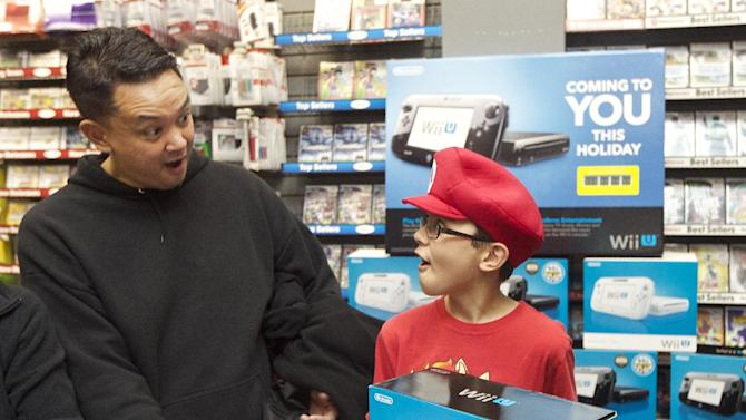 IMAGE DISTRIBUTED FOR NINTENDO -  Christopher Quiton, 12, right, and father Peter Quiton react to their Nintendo Wii U purchase at the GameStop Southcenter Mall store near Seattle, on Thursday Nov. 22, 2012. The Quitons were up early on Black Friday to get their hands on one of the hottest products this holiday season. (Photo by Stephen Brashear/Invision for Nintendo/AP Images)