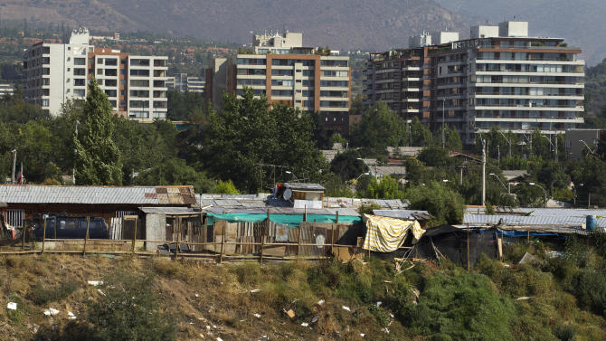 "Luxury apartment buildings in Las Condes' neighborhood are seen at background as the San Pablo shanty town is seen at front in Santiago, Chile, Wednesday, Jan. 23, 2013.  European, Latin American and Caribbean leaders gathering for this weekend's economic summit will likely see only one side of Chile _ the polished, upscale country where tourists and investors stay in five-star hotels in a sparklingly clean financial district nicknamed ""Sanhattan,"" well away from Santiago's slums. (AP Photo/Victor R. Caivano)"