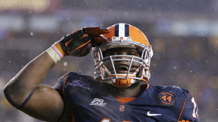 Syracuse linebacker Siriki Diabate salutes fans after he caused a safety in the first half of Syracuse's 38-14 victory over West Virginia in the Pinstripe Bowl NCAA college football game at Yankee Stadium in New York, Saturday, Dec. 29, 2012. (AP Photo/Kathy Willens)
