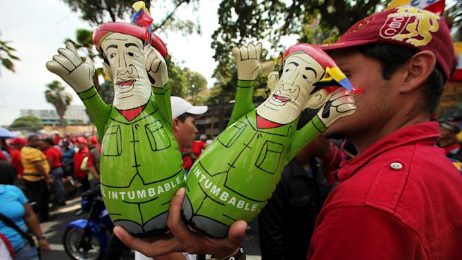 "A street vendor sells dolls of Venezuela's President Hugo Chavez called ""La Intumbable,"" or roughly ""One who cannot be toppled"" at a rally by Chavez supporters in Caracas, Venezuela, Wednesday, Jan. 23, 2013. The dolls have a weight at the bottom and when pushed, stand right back up. The cult of personality that Chavez long nurtured has been flourishing like never before as he confronts an increasingly difficult struggle against the mysterious cancer that afflicts him. (AP Photo/Fernando Llano)"