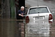 A man tries to remove a car from a flooded underpass at Faliro near Athens after a rainstorm Friday, Feb. 22, 2013. Hours of heavy rainfall in Athens caused extensive flooding, inundating basements and forcing authorities to close major roads and a central subway station. The Greek fire brigade says it received more than 900 calls to pump out water in the greater Athens region Friday. (AP Photo/Kostas Tsironis)