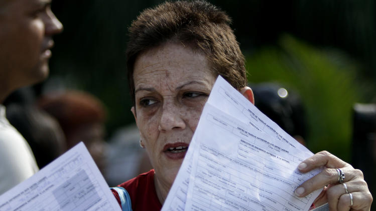 In this Jan. 7, 2013 photo, a woman holds papers after filling out a passport application outside an immigration office in Havana, Cuba. In the past nearly all exit visa applications were granted, and relatively quickly, but the costs were prohibitive to many in this country where wages average $20 a month. Between notarization and application fees, fees ran to $300 or more per trip, and some Cubans paid an additional $200 to $300 to people overseas for invitation letters. Now, with a new law taking effect Monday, Jan. 14, 203, islanders need only make a one-time $100 application for a passport, renewable for $20 every two years.  (AP Photo/Franklin Reyes)