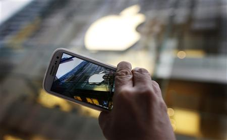 A passerby photographs an Apple store logo with his Samsung Galaxy phone in central Sydney in this September 21, 2012, file photo. REUTERS/Tim Wimborne/Files