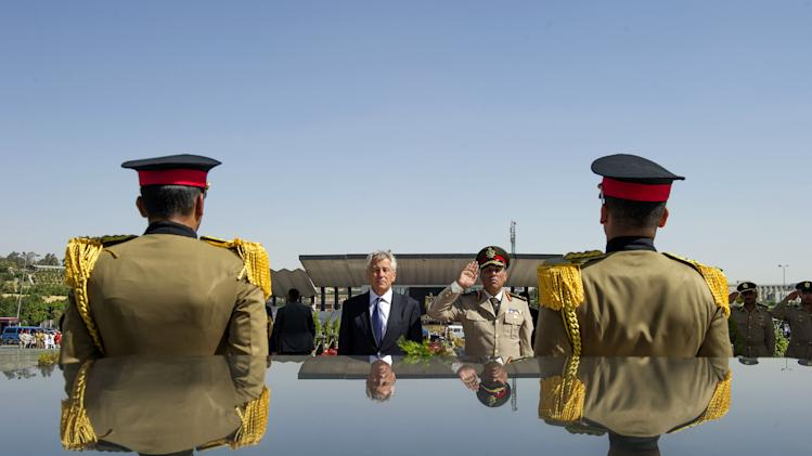 FILE - In this Wednesday, April 24, 2013, file photo, U.S. Secretary of Defense Chuck Hagel, second left, stands with an Egyptian army official before laying a wreath at the tomb of late President Anwar al-Sadat in Cairo. U.S. officials said Wednesday, Oct. 9, 2013, that the Obama administration is poised to slash hundreds of millions of dollars in military and economic assistance to Egypt. The U.S. has been considering such a move since the Egyptian military ousted the country's first democratically elected leader in June. (AP Photo/Jim Watson, Pool, File)