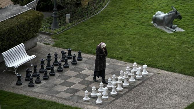 A member of the Iranian media walks on an open air chess board at the site of negotiations about Iran's nuclear program, between Iran officials and representatives of the world powers, Monday March 30, 2015 in Lausanne, Switzerland. Negotiations over Iran's nuclear program entered a critical phase on Monday with substantial differences still remaining less than two days before a deadline for the outline of an agreement.  (AP PHOTO / POOL, Brendan Smialowski)