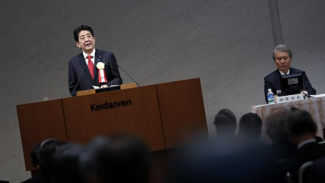 Japan's Prime Minister Abe speaks next to Japan Business Federation's Chairman Sakakibara during a year end meeting at Keidanren in Tokyo