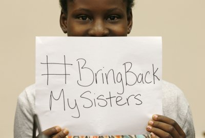 CLICK for slideshow: Nigerian teenager Deborah Peters, the sole survivor of a Boko Haram attack on her family in 2011, holds up a sign referring to th...