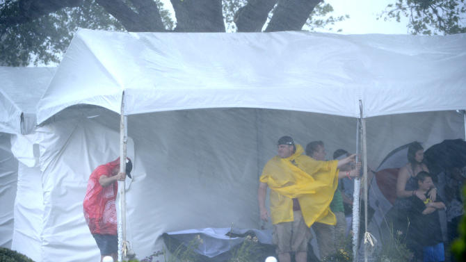 Spectators take cover under a vendor tent behind the first tee as a sever thunderstorm rolls through during the final round of the Arnold Palmer Invitational golf tournament in Orlando, Fla., Sunday  March 24, 2013.(AP Photo/Phelan M. Ebenhack)