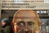 A woman is reflected in glass covering a copy of news paper featuring crying Vladimir Putin in Moscow. The Russian opposition Tuesday defiantly vowed to wage a sustained campaign of protests after police detained hundreds in rallies against Putin's crushing victory in presidential polls
