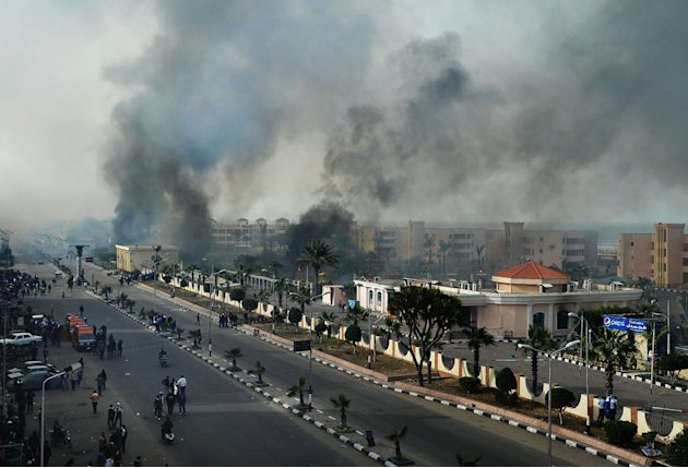 Smoke rises after Egyptian protesters clash with police, unseen, in Port Said, Egypt, Sunday, Jan. 27, 2013.  Violence erupted briefly when some in the crowd fired guns and police responded with volle