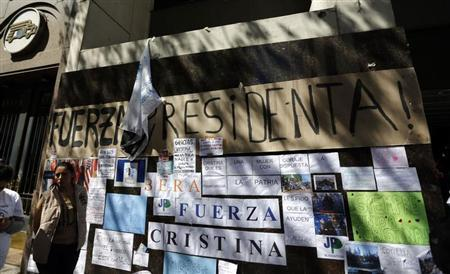 A woman waits next to signs in support of Argentina's President Fernandez outside the hospital where she had surgery in Buenos Aires