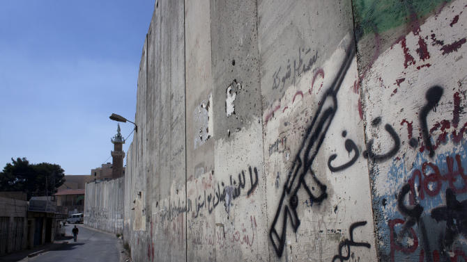 """In this photo taken Monday, Sept. 9, 2013, a Palestinian man walks by a barrier separating the West Bank town of Abu Dis, from east Jerusalem with Arabic graffiti that reads, """"PLO, no for negotiations,"""" seen on the side of Abu Dis, West Bank. Twenty years after the two sides signed the Declaration of Principles on the White House lawn, the words that launched Israeli-Palestinian talks on dividing the Holy Land into two states ring hollow to many on both sides. Negotiators said mistakes they made then cause damage to this day. PLO refers to the Palestine Liberation Organization. (AP Photo/Nasser Nasser)"""