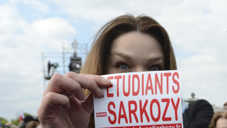 "Carla Bruni-Sarkzoy, the wife of French President and UMP party candidate for the election Nicolas Sarkozy, holds up a sticker reading ""Students for Sarkozy"" in front of her face during a campaign rally at the Place de la Concorde in Paris, Sunday, April 15, 2012. Nicolas Sarkozy and his chief challenger for the presidency, Francois Hollande, held rallies on opposite sides of Paris in their last big campaign meeting in the capital before voting begins. (AP Photo/Eric Feferberg, Pool)"