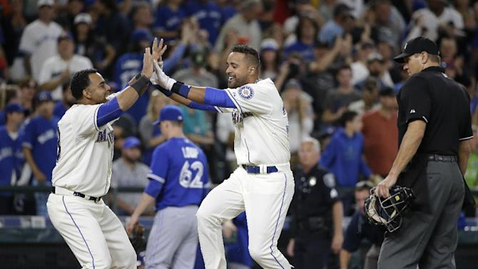 Seattle Mariners' Franklin Gutierrez, right, is greeted at home by Nelson Cruz on his home run against the Toronto Blue Jays in the 10th inning of a baseball game Sunday, July 26, 2015, in Seattle. The Mariners won 6-5. (AP Photo/Elaine Thompson)