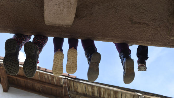 Children sit on a balcony waiting for carnival celebrations in the Navarran village of Lantz