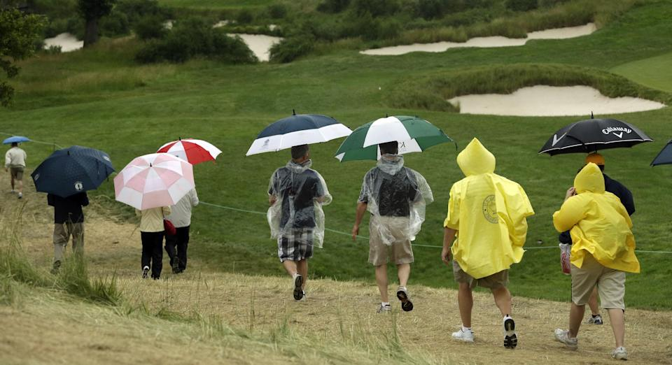 Spectators walk off the course as a weather warning delays the first round of the U.S. Open golf tournament at Merion Golf Club, Thursday, June 13, 2013, in Ardmore, Pa. (AP Photo/Gene J. Puskar)