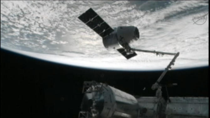 This image from NASA-TV shows the capture of the Dragon capsule by a robot arm on the International Space Station as they passed over the South Atlantic Ocean early Wednesday Oct. 10, 2012. It's the first official delivery by the California-based SpaceX company under a $1.6 billion contract with NASA. The contract calls for 12 such shipments. (AP Photo/NASA)