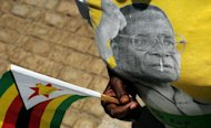 A mourner wears a shirt bearing an image of Zimbabwe President Robert Mugabe during a funeral ceremony for John Landa Nkomo at the National Heroes Acre in Harare, on January 21, 2013. Mugabe has used the funeral of his vice president to again call for peace and calm at upcoming elections