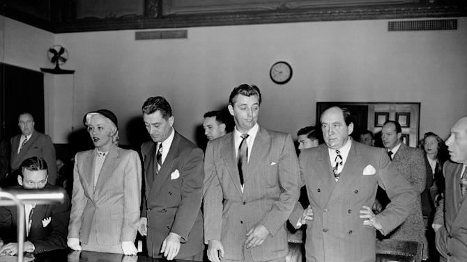 """FILE - In this Feb. 9, 1949 file photo, actor Robert Mitchum, center right, and actress Lila Leeds, left, are sentenced to 60 days in jail on charges of conspiracy to possess marijuana cigarettes in Los Angeles. On the occasion of  """"Legalization Day,"""" Thursday, Dec. 6, 2012, when Washington's new law takes effect, AP takes a look back at the cultural and legal status of the """"evil weed"""" in American history. (AP Photo, File)"""