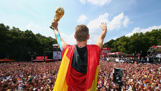"German soccer player Bastian Schweinsteiger celebrates on stage at the German team victory ceremony , near the Brandenburg Gate in Berlin,  Tuesday July 15,  2014.  Germany's World Cup winners shared their fourth title with hundreds of thousands of fans by parading the trophy through cheering throngs to celebrate at the Brandenburg Gate on Tuesday. An estimated 400,000 people packed the ""fan mile"" in front of the Berlin landmark to welcome home coach Joachim Loew's team and the trophy  which returned to Germany for the first time in 24 years"