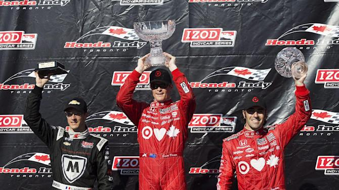 Winner Scott Dixon, center, along with second-place Sebastien Bourdais, left, and Dario Franchitti, right, celebrate after the IndyCar auto race in Toronto on Saturday, July 13, 2013. Franchitti was handed the third-place trophy only to learn sometime during the podium celebration he'd been stripped of the finish for blocking Will Power on the final lap. (AP Photo/The Canadian Press, Michelle Siu)