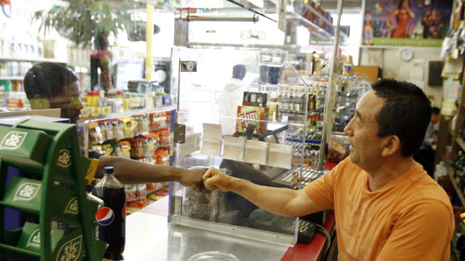 In this Friday April 20, 2012 photo, James Oh, right, owner of Tom's Liquor on the corner of Florence and Normandie, greets a customer in his store in South Los Angeles. In the 20 years since the 1992 riots, residents of the city's largely black and Hispanic South Side complain that the area still is plagued by too few jobs, too few grocery stores and a lack of redevelopment that would bring more life to the area. (AP Photo/Matt Sayles)