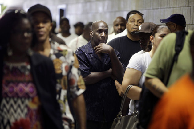 FILE - In this Tuesday, Aug. 21, 2012 file photo, job seekers wait in line at a construction job fair in New York. The U.S. economy is weak and the job market brutal. President Barack Obama wants to create jobs with government spending on public works and targeted tax breaks to businesses. Mitt Romney aims to generate hiring by keeping income taxes low, slashing corporate taxes, relaxing or repealing regulations on businesses and encouraging production of oil and natural gas. (AP Photo/Seth Wenig, File)