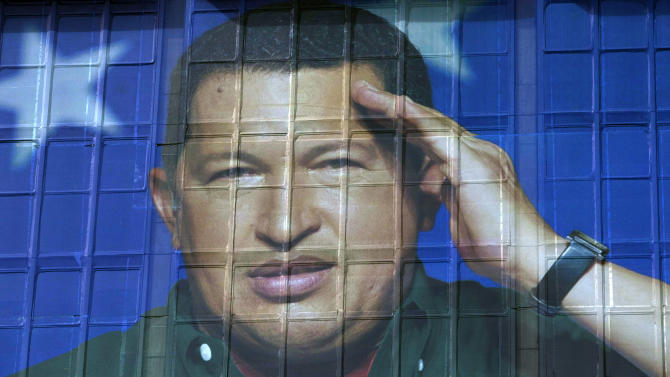 An image of Venezuela's President Hugo Chavez covers the headquarters of the state-run oil company in Caracas, Venezuela, Thursday, March 1, 2012. Chavez on Thursday made his first live communication with news media since undergoing surgery this week to remove a possibly cancerous tumor. Chavez has been in Cuba since last Friday to have a growth removed in the same part of the pelvis where a larger, malignant tumor was extracted last year.  (AP Photo/Ariana Cubillos)