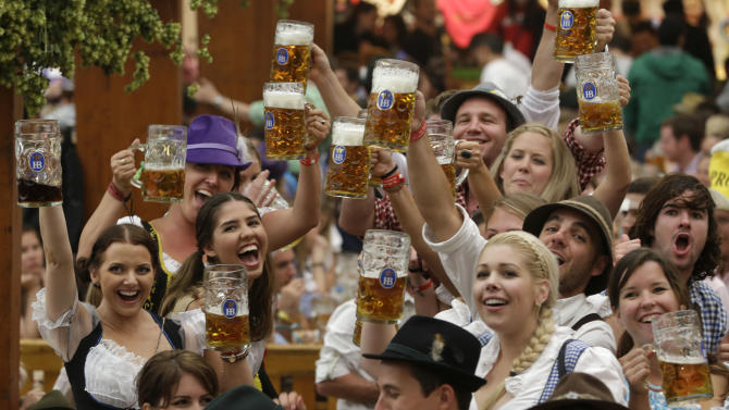 """Young people enjoy the opening ceremony of the famous Bavarian """"Oktoberfest"""" beer festival in Munich, southern Germany, Saturday, Sept. 22, 2012. The world's largest beer festival, to be held from Sept. 22 to Oct. 7, 2012 will see some million visitors. (AP Photo/Matthias Schrader)"""