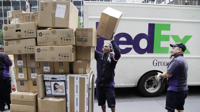 In this Friday, May 11, 2012, file photo, FedEx workers sort boxes for delivery as they are unloaded from a FedEx truck in New York. FedEx Corp. said Tuesday, June 19, 2012, that slow global growth will crimp its earnings results over the next 12 months, but it's vowing to make significant cost cuts to make up for any shortfall.(AP Photo/Mark Lennihan)